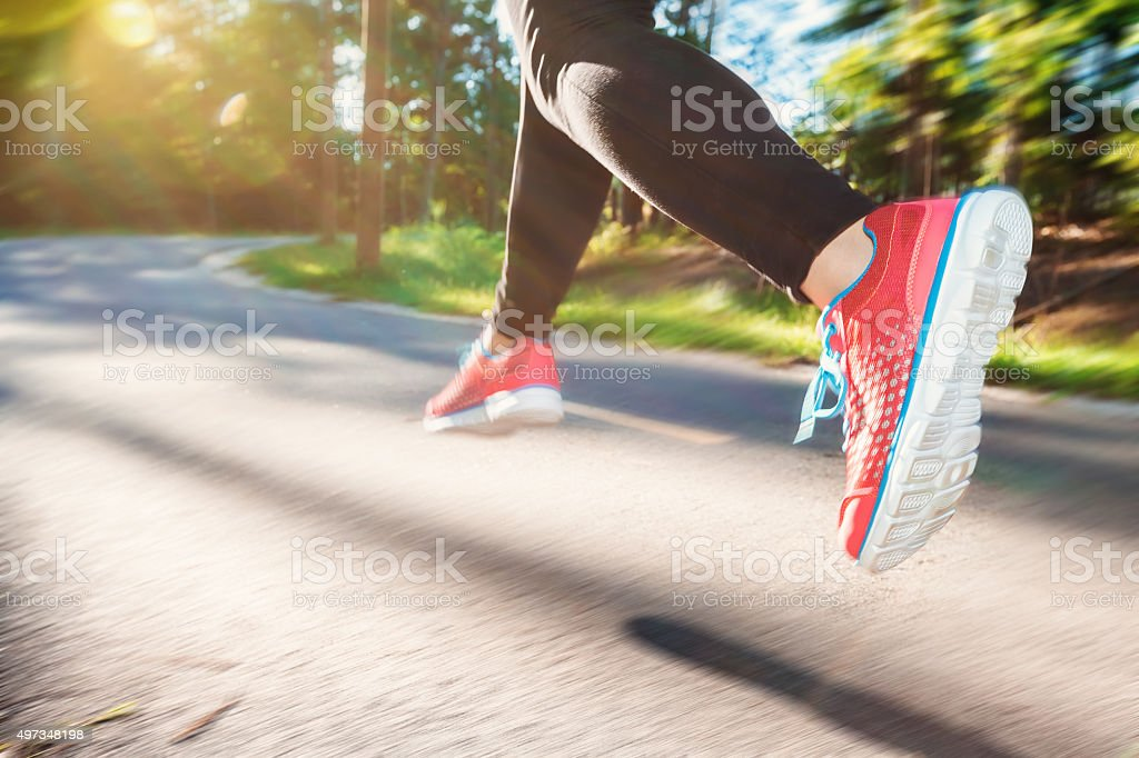 Woman jogging down an outdoor trail stock photo