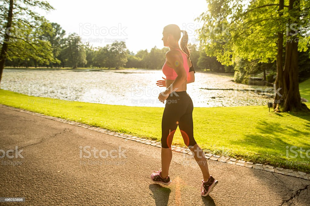 Woman jogging in park stock photo