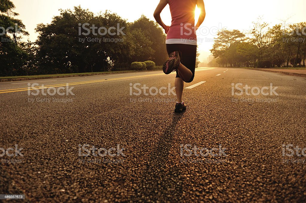 Woman jogging on road stock photo