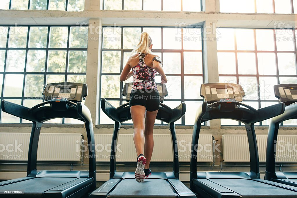Woman jogging on treadmill stock photo