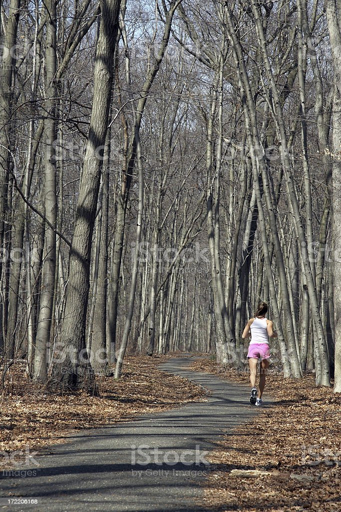 woman jogging on wooded trail stock photo