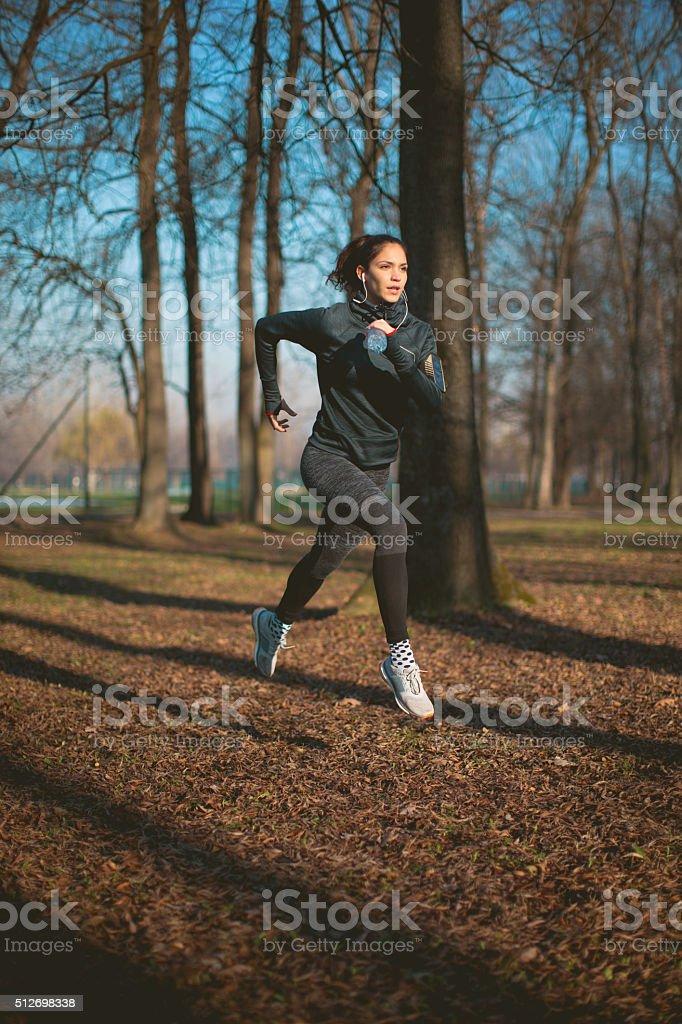 Woman jogging through park stock photo
