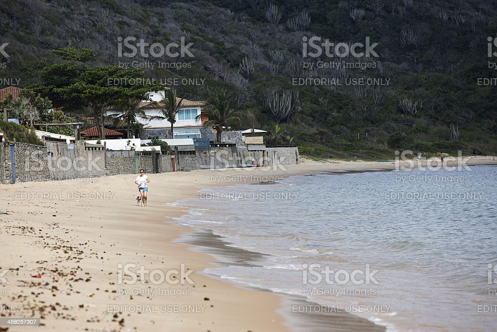 Woman jogging with her dog on Buzios beach royalty-free stock photo