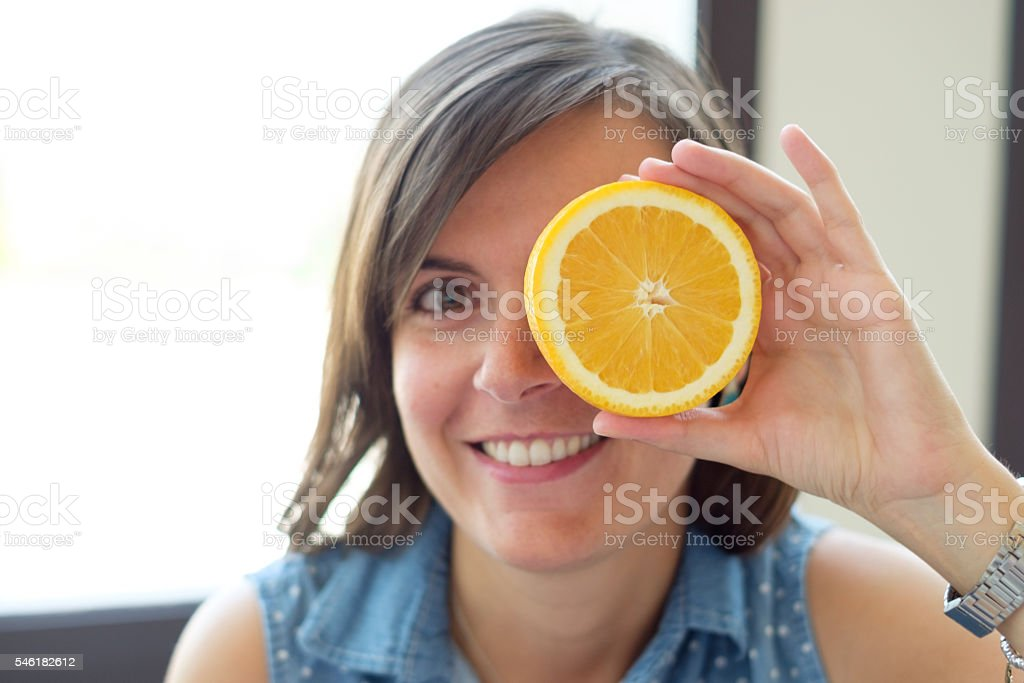 Woman joking with a slice of orange stock photo