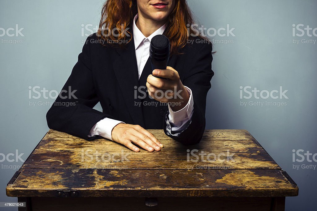 Woman journalist is pointing microphone at camera royalty-free stock photo