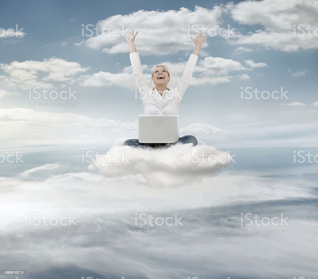 Woman joyfully floating in the clouds while on a laptop stock photo