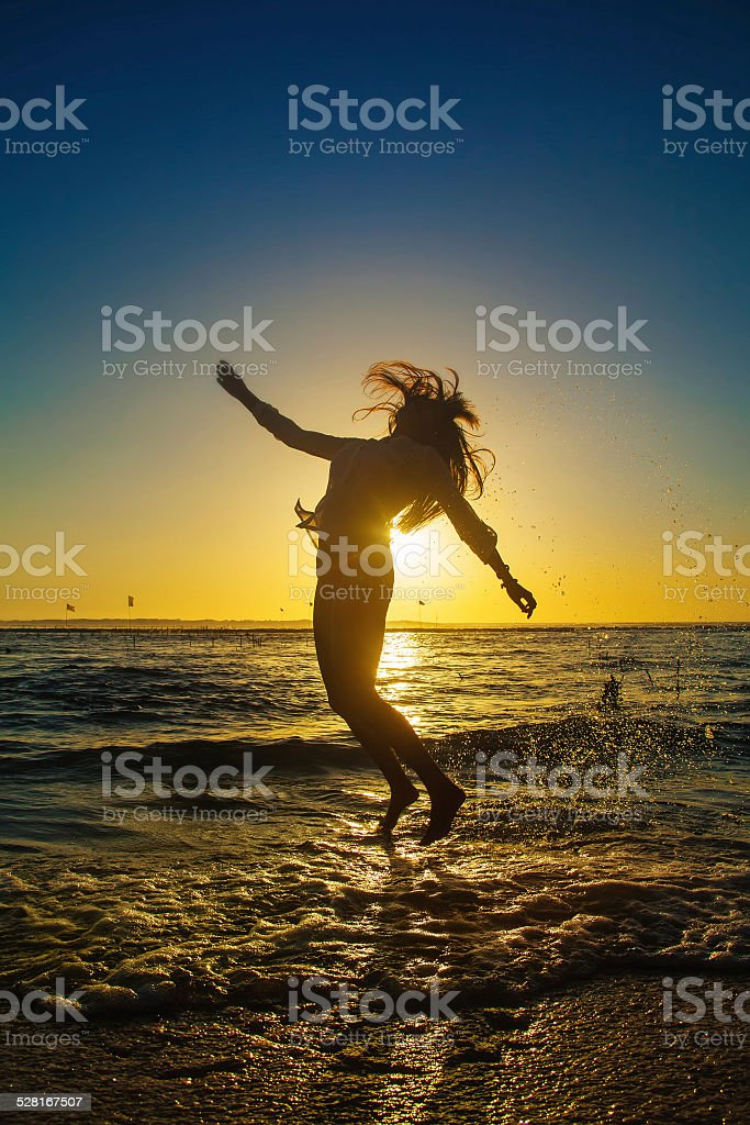 Woman jumping against sunset sky stock photo