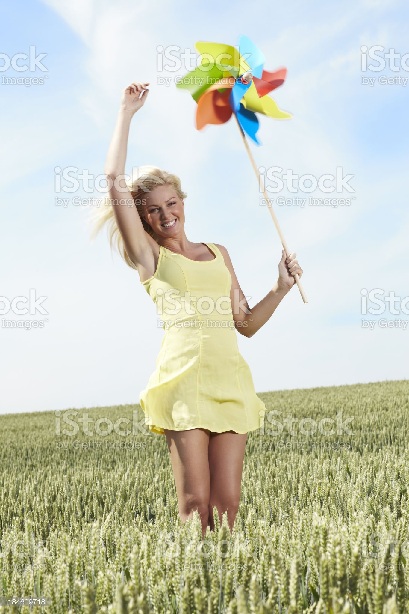 woman jumping and holding windmill up in the sky royalty-free stock photo