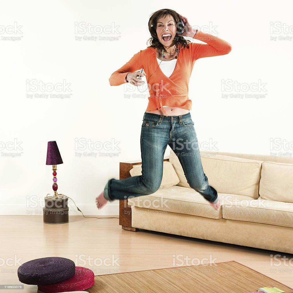 Woman jumping and listening music stock photo