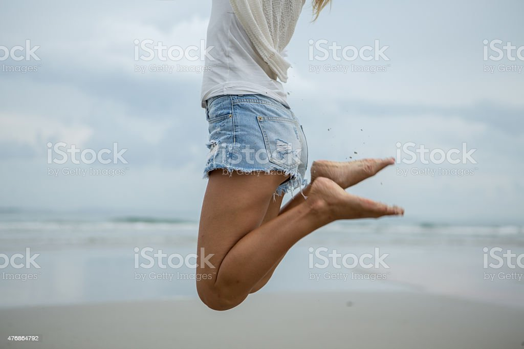 Woman jumping at the beach for positive emotion stock photo