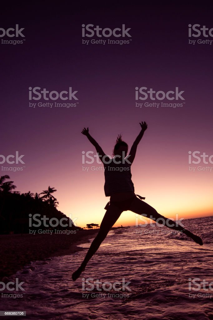 Woman jumping at the beach stock photo