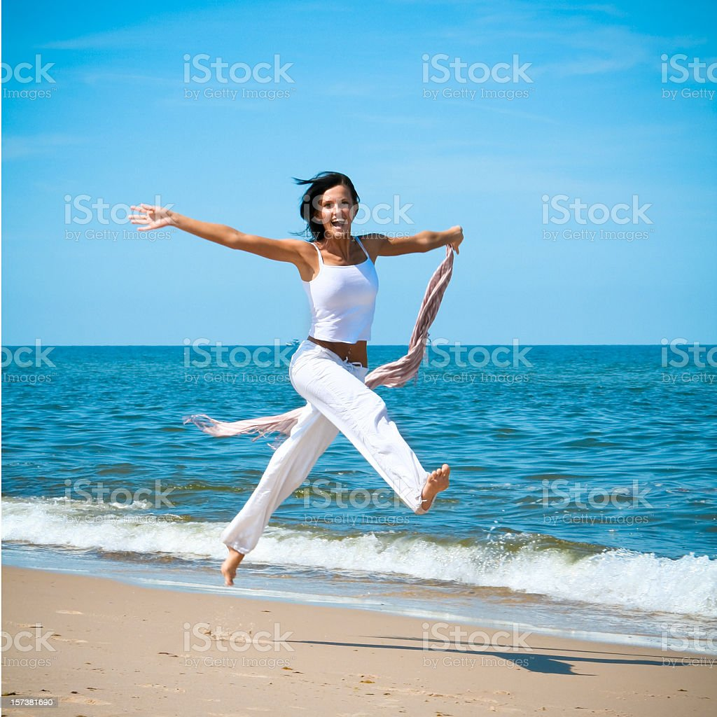 Woman jumping happily on the beach royalty-free stock photo