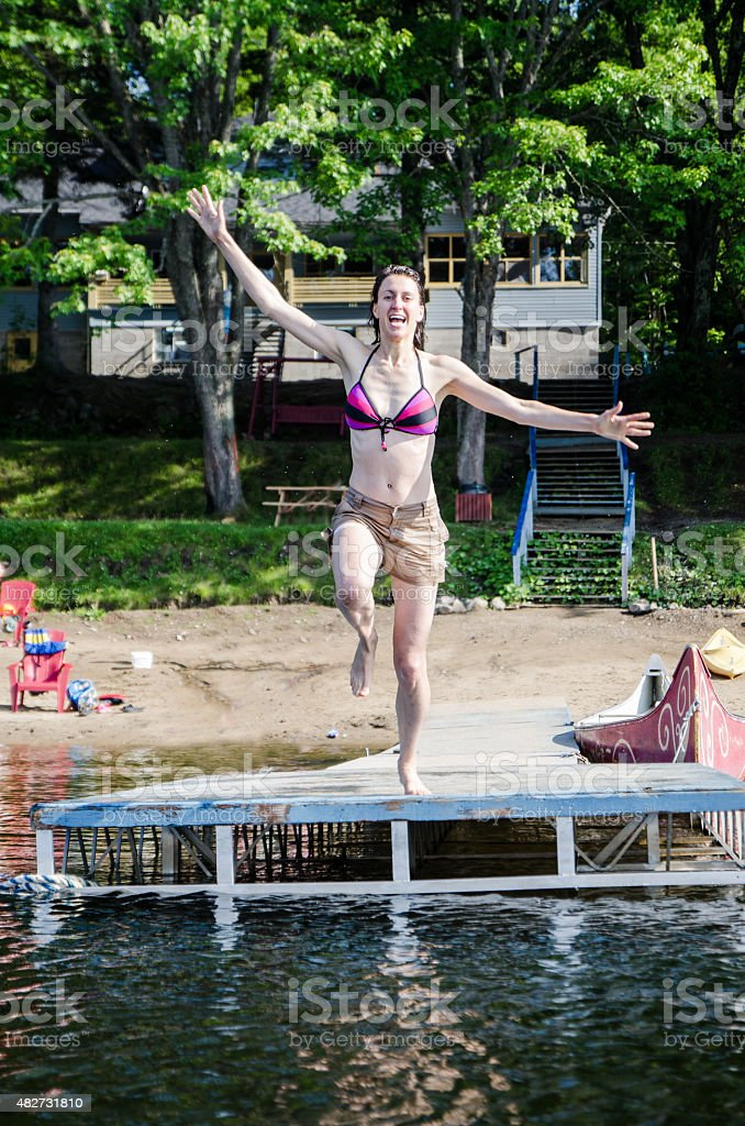 Woman jumping in lake from dock stock photo