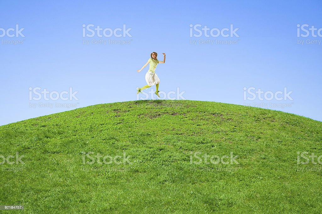 woman jumping on a green meadow royalty-free stock photo