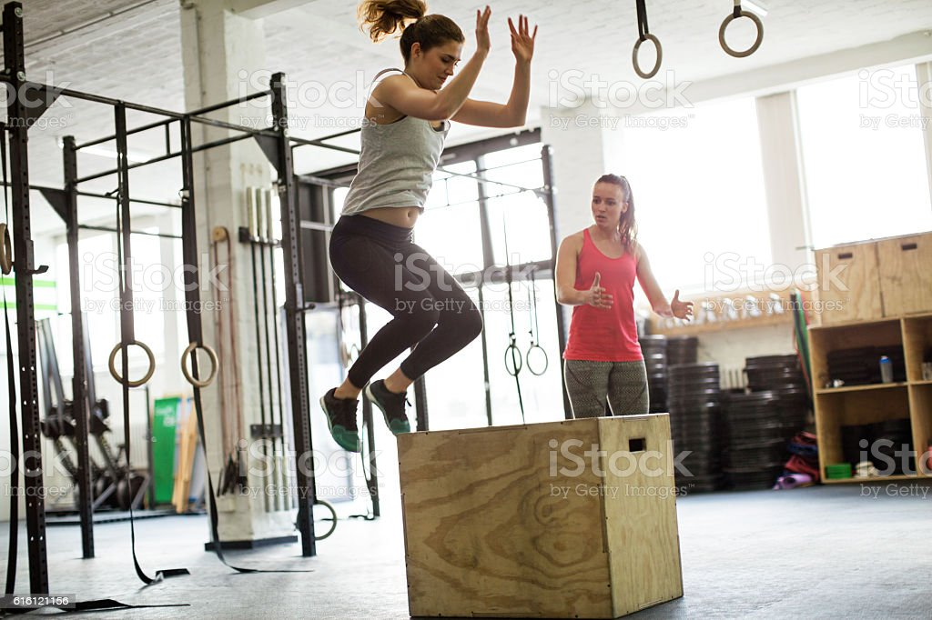 Woman jumping on box with fitness trainer stock photo
