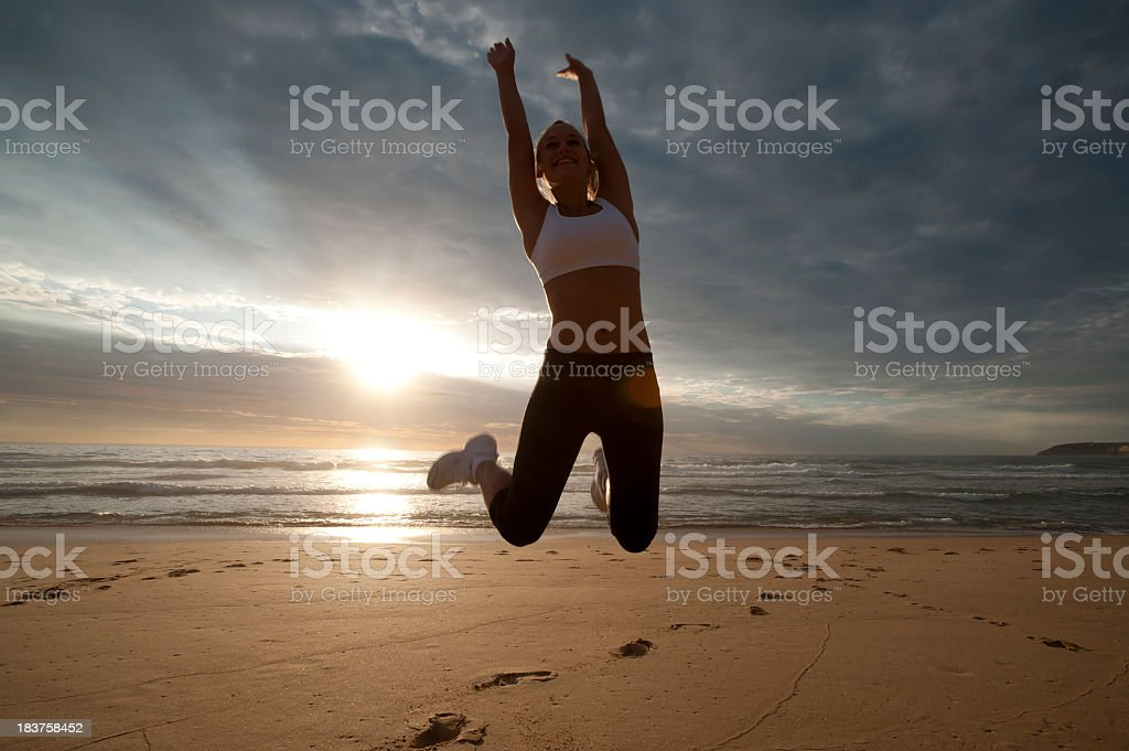 Woman jumping on the beach royalty-free stock photo