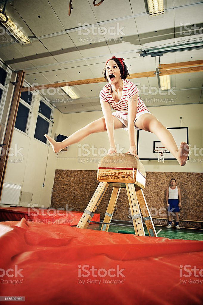 Woman jumping over a buck stock photo