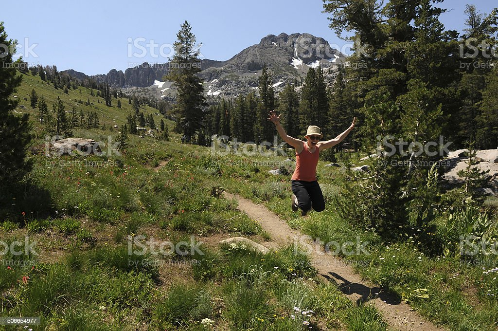 Woman Jumping Over a Hiking Trail royalty-free stock photo