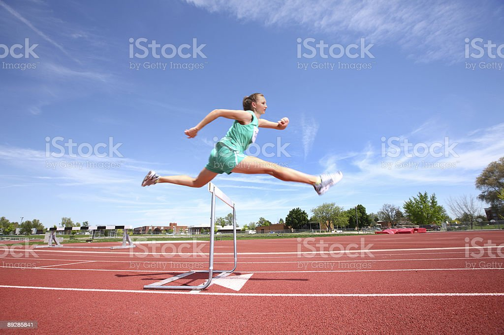 Woman jumping over hurdle stock photo