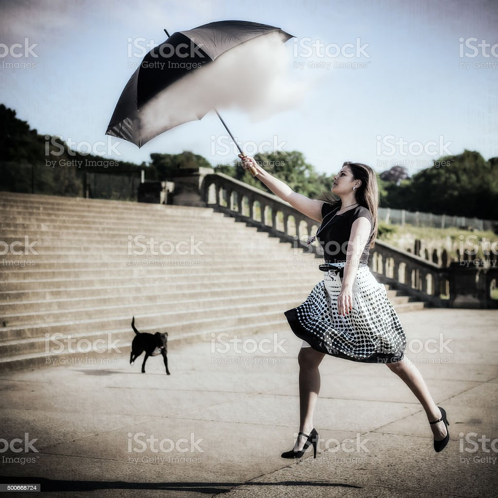 Woman Jumping Up And Catching Cloud With Umbrella stock photo
