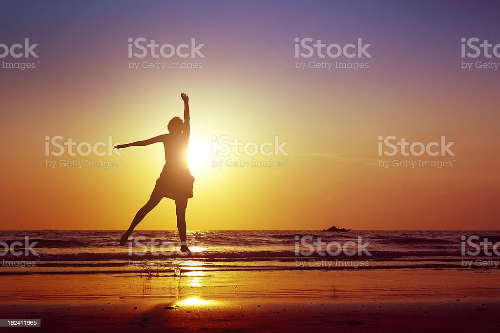 A woman jumping up on a beach  royalty-free stock photo