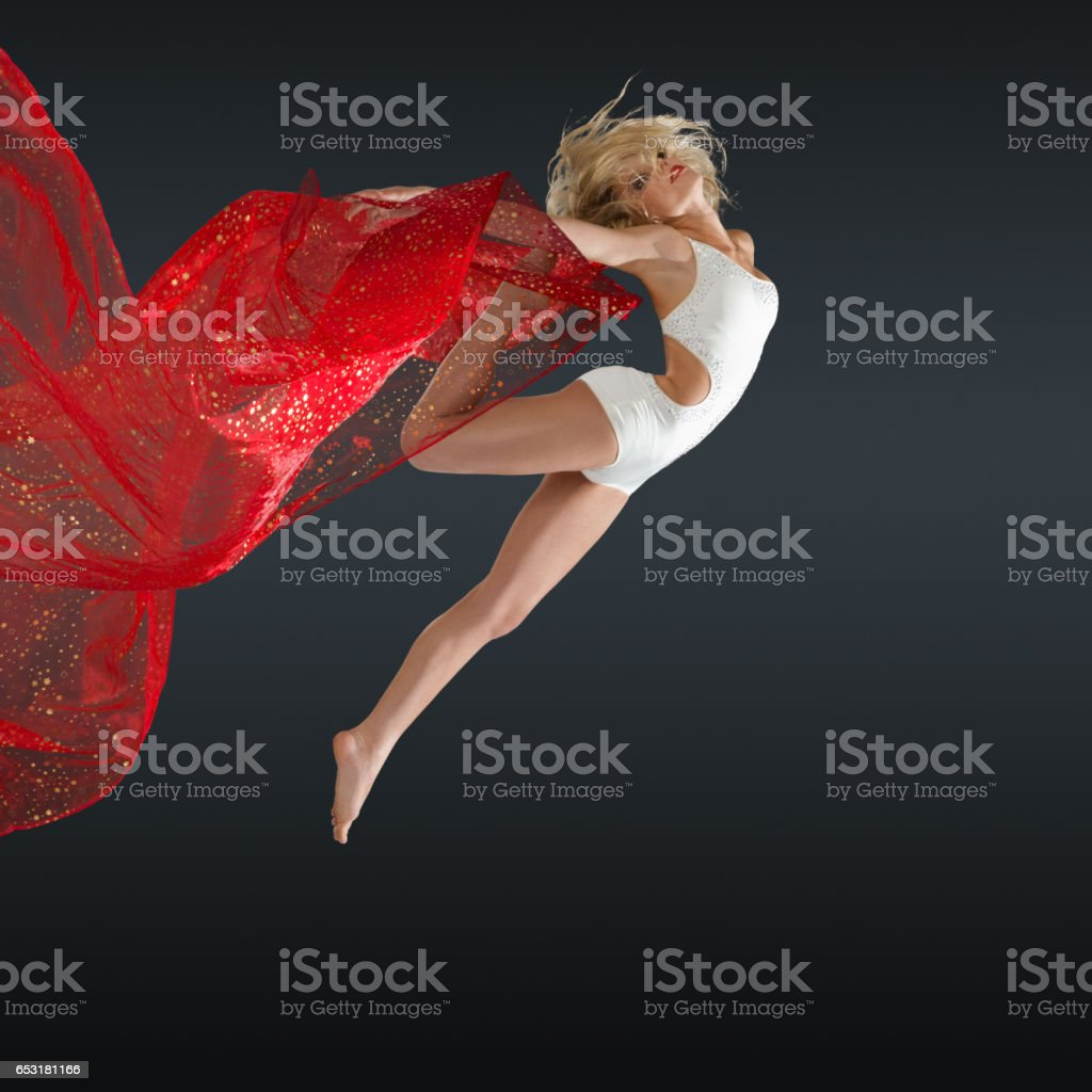 Woman jumping with silk fabric stock photo