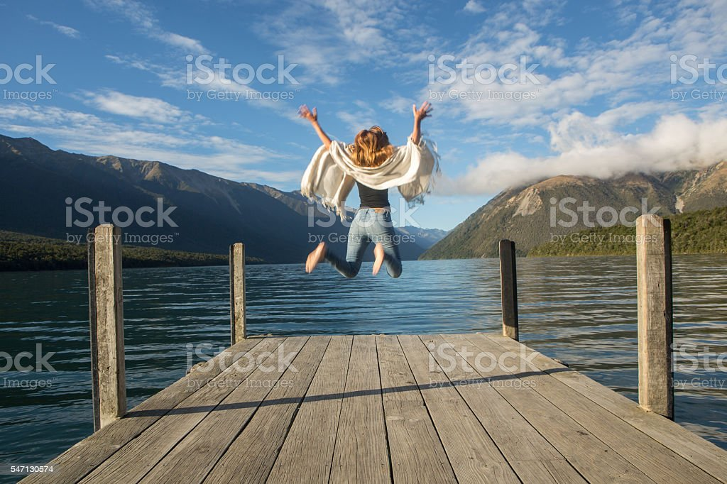 Woman jumps in the air on lake pier stock photo