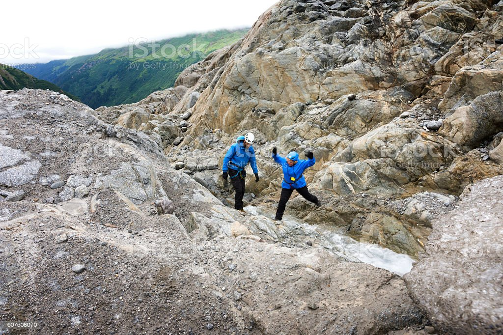 Woman jumps over creek at glacier terminus stock photo