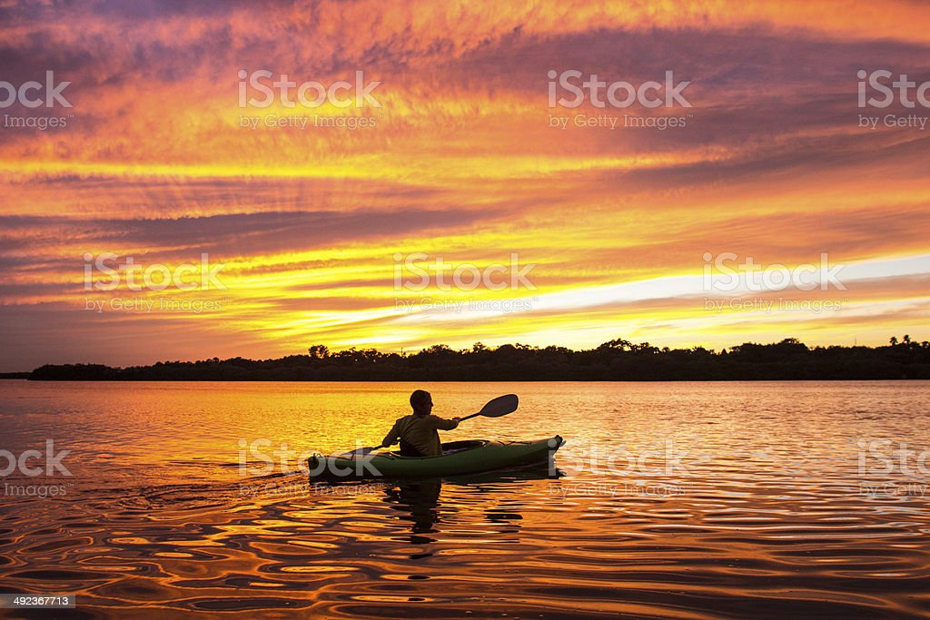 Woman Kayaking at Sunset stock photo
