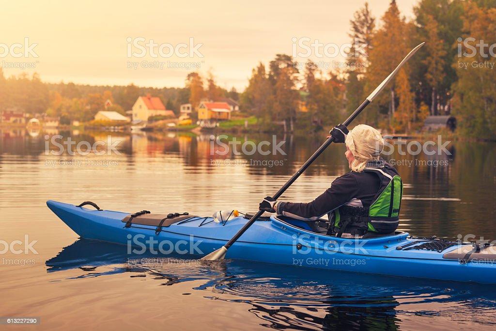 Woman kayaking on a lake stock photo