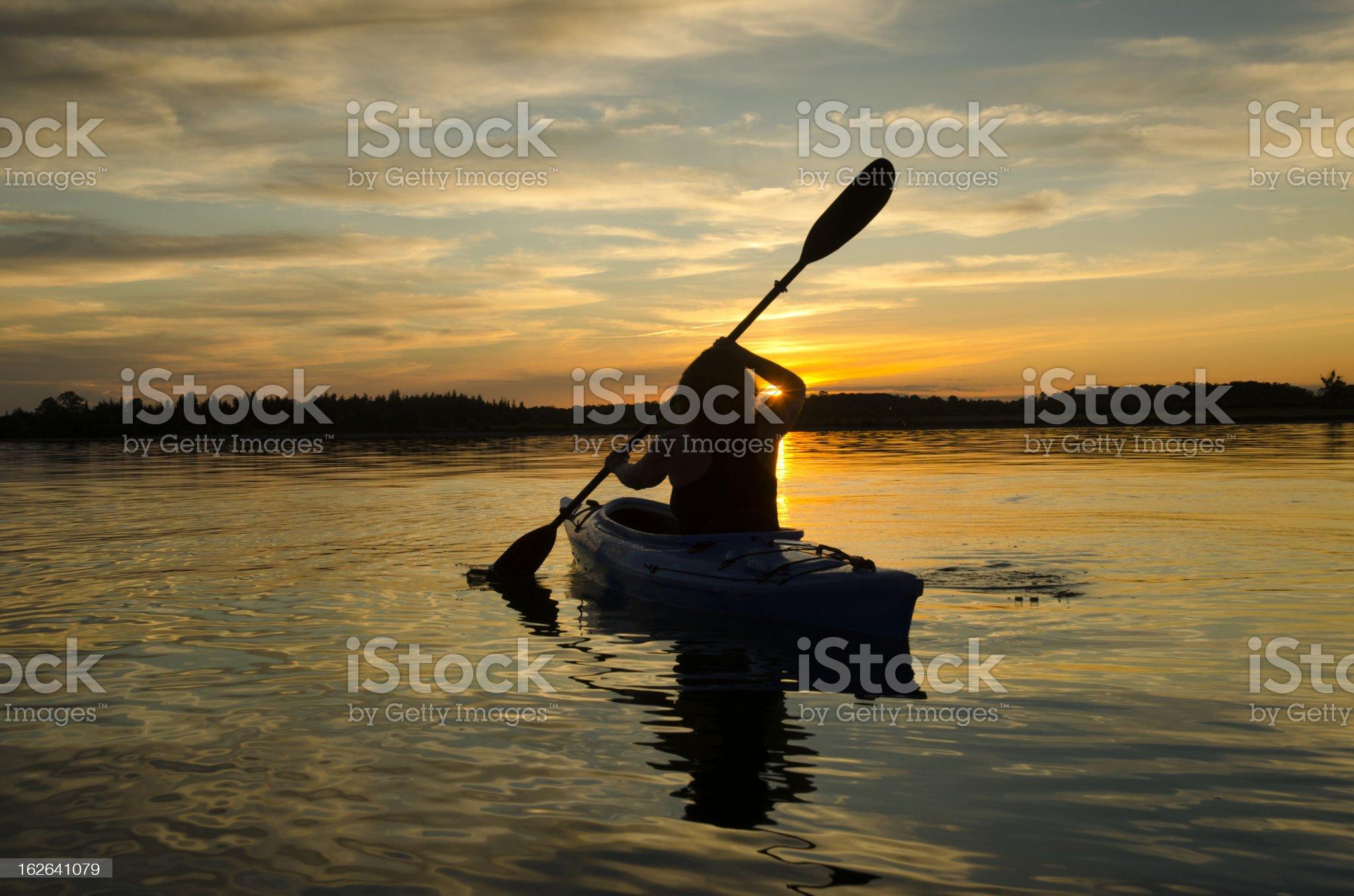 Woman Kayaks at Sunset royalty-free stock photo