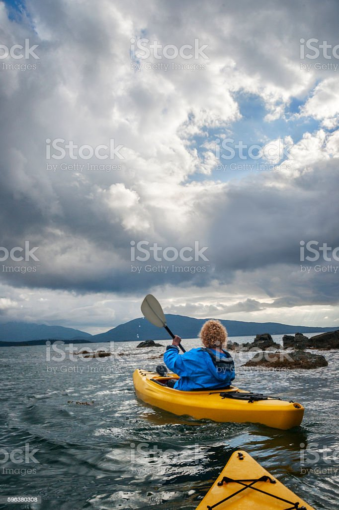 Woman kayaks out to sea in Gulf of Alaska stock photo