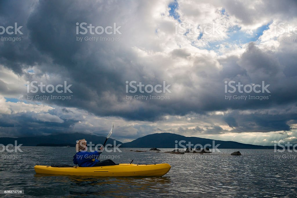 Woman kayaks tranquil cove in Juneau stock photo
