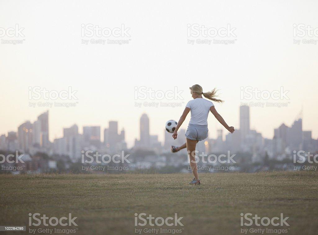 Woman kicking soccer ball in urban park royalty-free stock photo