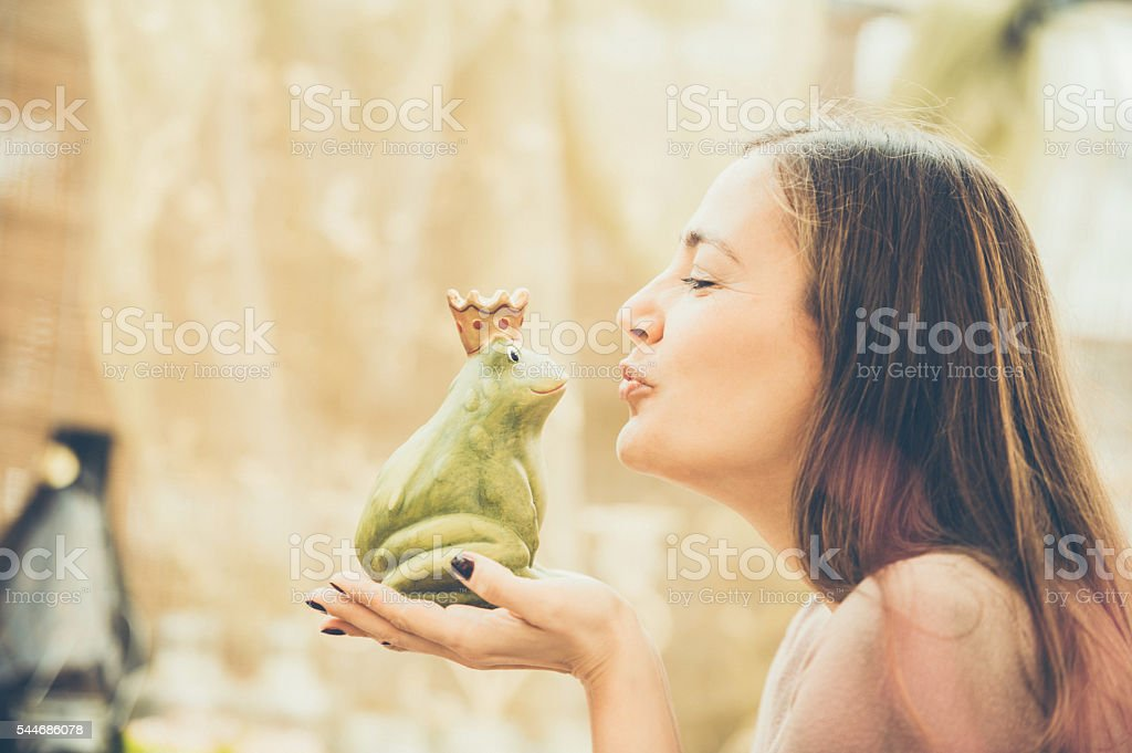 Woman kissing a frog stock photo