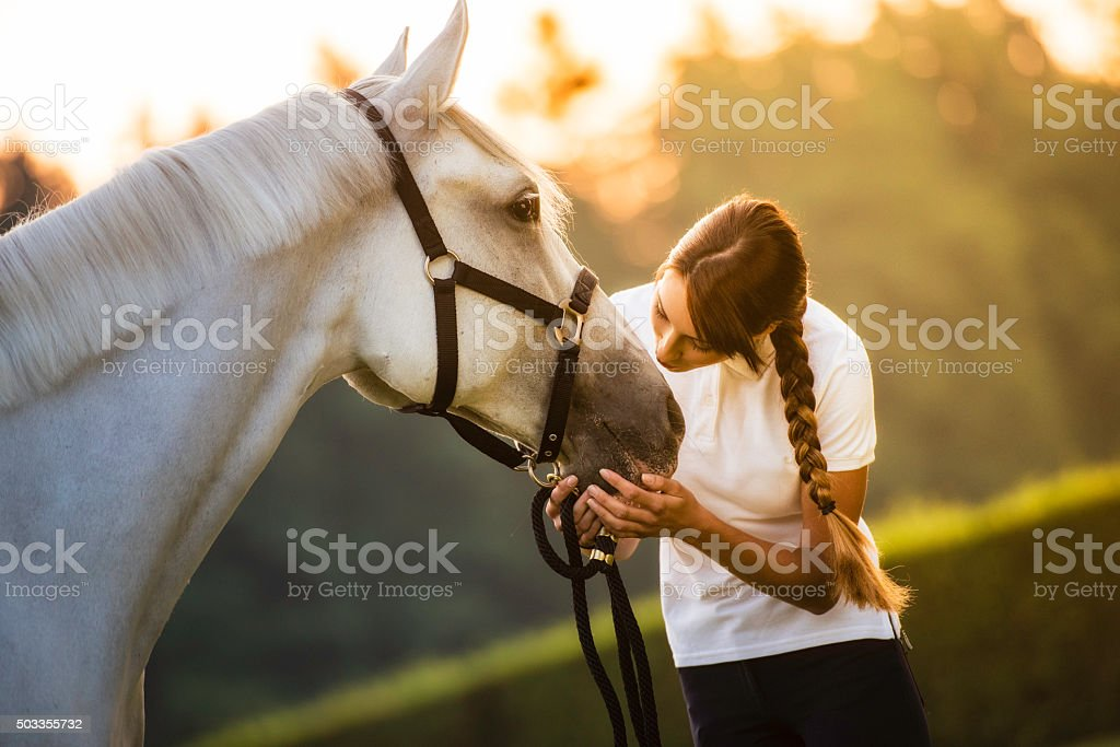 Woman kissing a horse on the head in nature stock photo