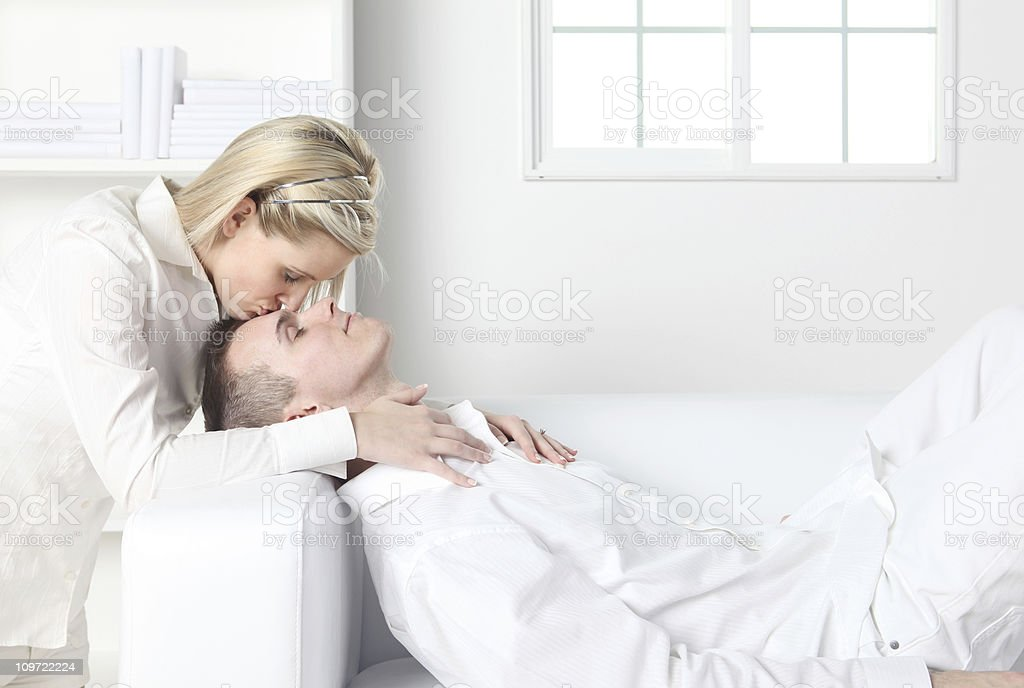 Woman kissing a man on forehead royalty-free stock photo