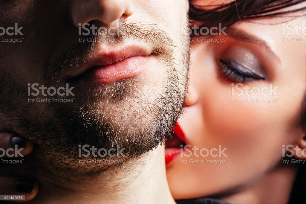 Woman kissing a man on the neck stock photo
