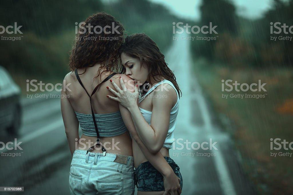 Woman kissing a woman's shoulder. stock photo