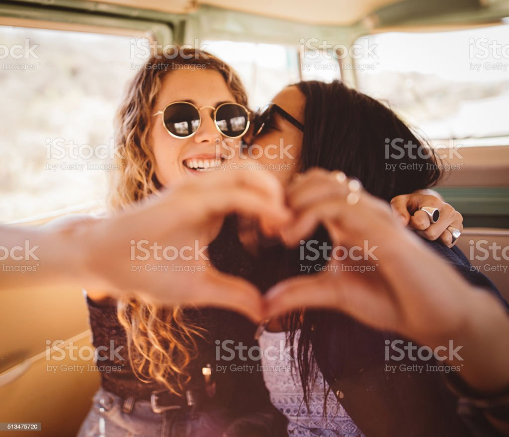 Woman kissing her girl friend on cheek with hand heart stock photo