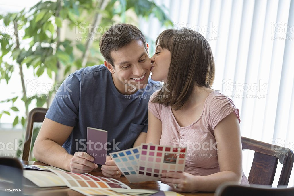 Woman Kissing Man While Choosing Color From Catalogs stock photo