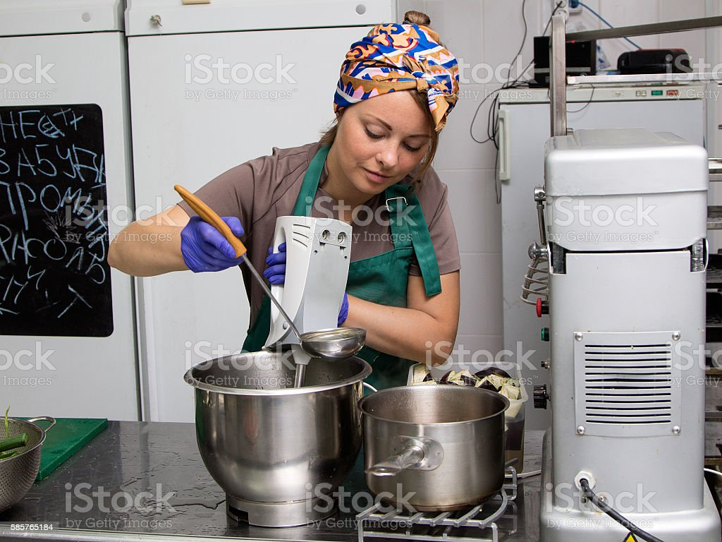 Woman kitchener mixing food in the pan stock photo