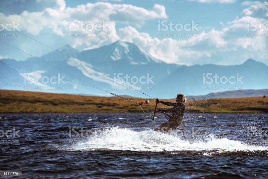 Woman kite surfing in mountain lake stock photo