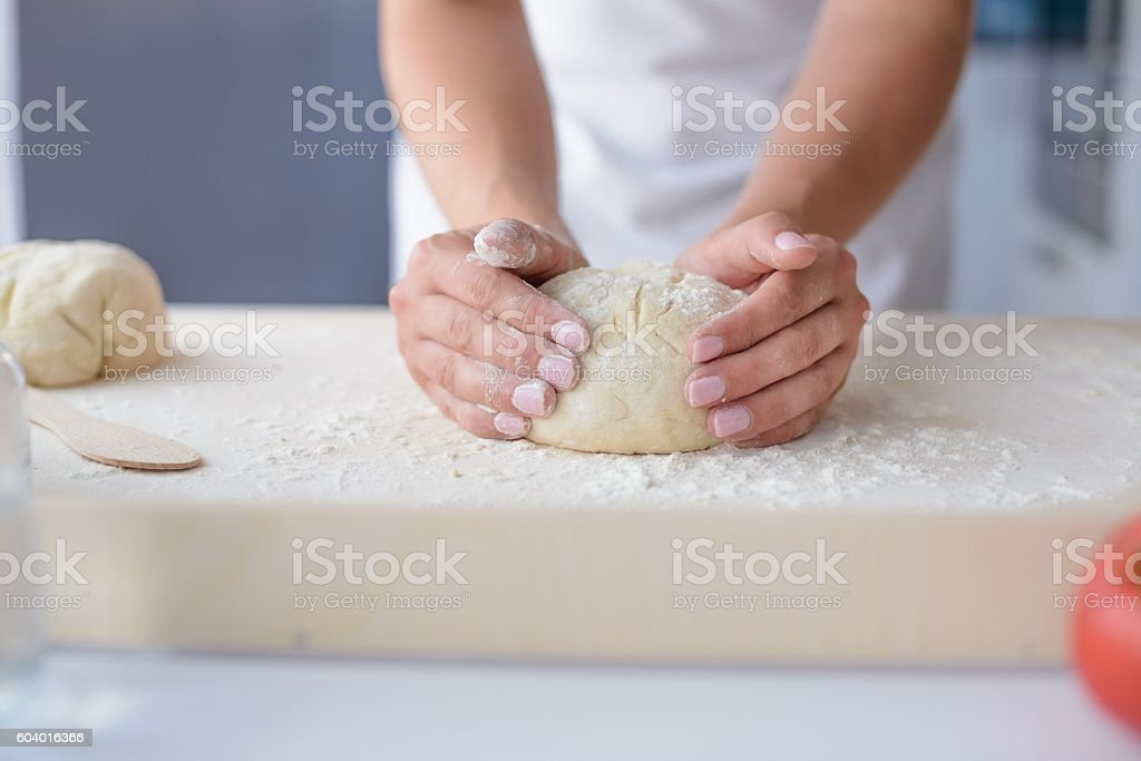 Woman kneading pizza dough on wooden pastry board. Woman doing...