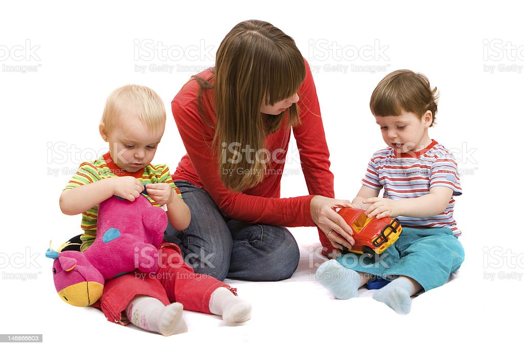 Woman kneeling between two toddlers playing stock photo