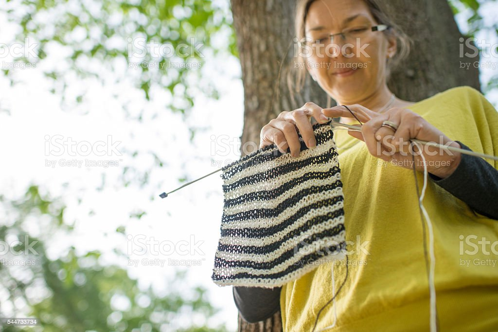 Woman knitting outdoors. stock photo
