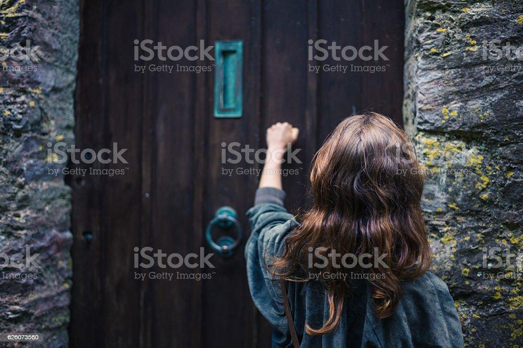Woman knocking on door stock photo