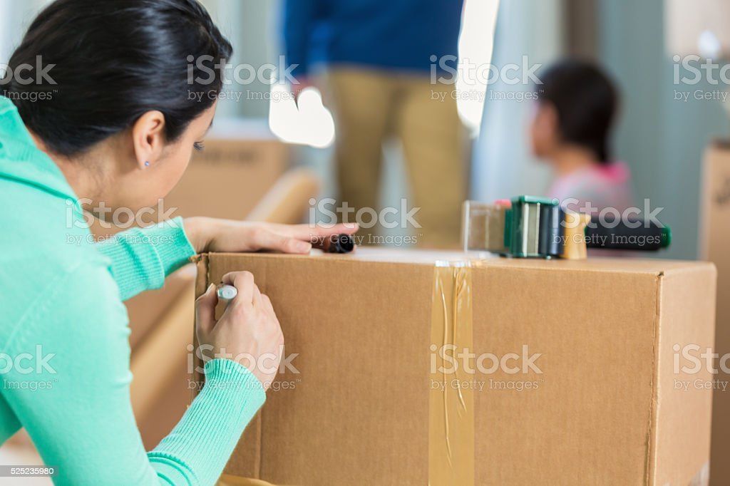 Woman labels moving box stock photo