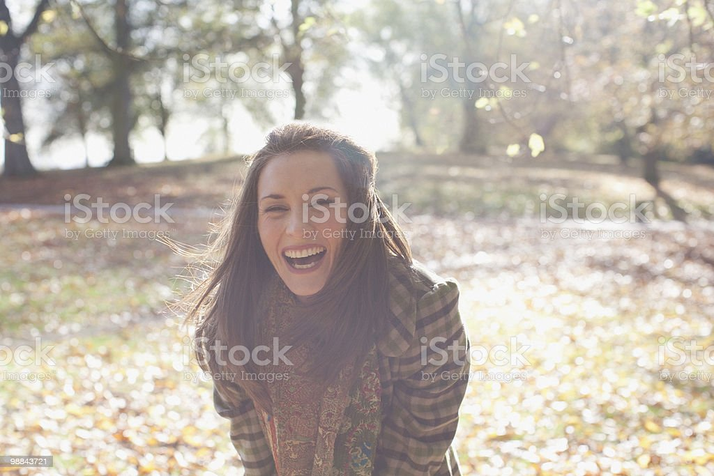 Woman laughing outdoors in autumn leaves stock photo