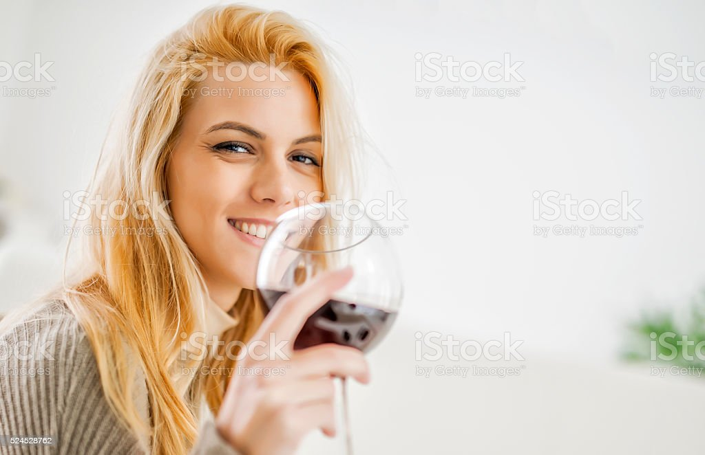 Woman laughing while holding a glass of wine stock photo